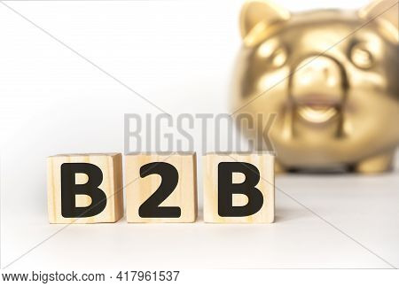 Text B2B On Wooden Cube Blocks. Background Happy Smiling Gold Piggy Bank On Table. Financial Goal, B