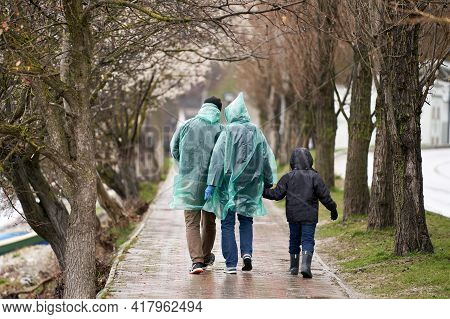 A Family Of Three Strolls Down An Alley In The Rain. The Parents Are Wearing Disposable Raincoats, T