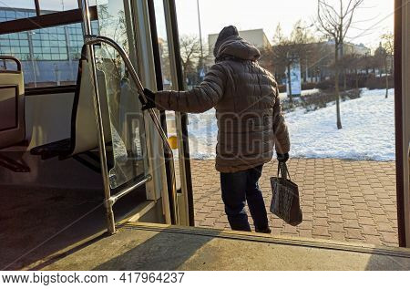Woman Passenger With Jeans And Coat Jacket With Hand Bag Getting Off The Bus During Winters. Female
