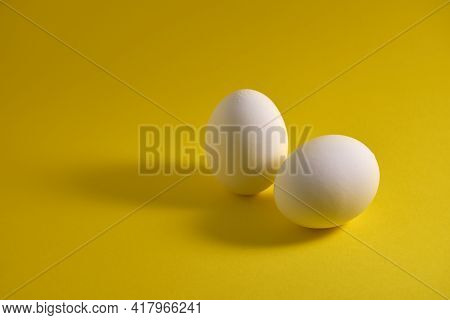 Chicken Eggs And Eggshells On A Yellow Background.