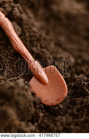 Farming Agriculture Concept With Toy Plastic Shovel In Plowed Fertile Soil Ground Land Macro Close U