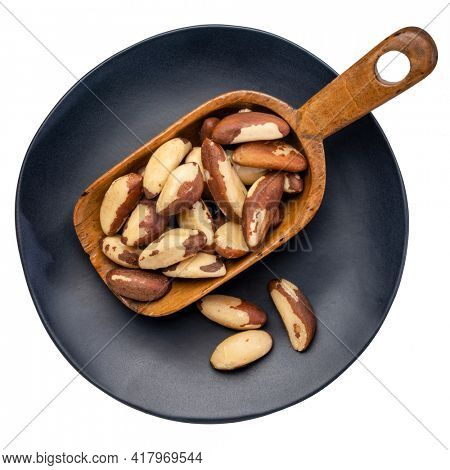 shelled brazilian nuts in a vintage wooden scoop on isolated black ceramic plate, top view