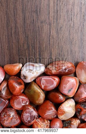 South Onyx Heap Jewel Stones Texture On Half Brown Varnished Wood Background. Place For Text.