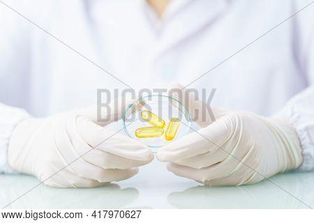 Close Up Scientist Holding Omega 3 Capsule In Labcoat