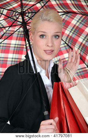 Female shopper under a brolly