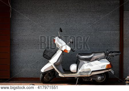 A Vintage  White   Motorcycle, Moped  Stands In A Parking Against The Backdrop Of  Gray Wall. Side V