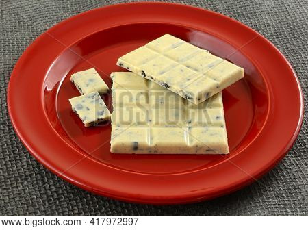 White Chocolate Bar With Bits Of Chocolate Cookies On Red Snack Plate On Gray Burlap