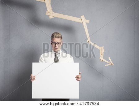Concept: Business crisis. Worried businessman holding white empty signboard with space for text in front of business graph with negative trend, isolated on grey background.