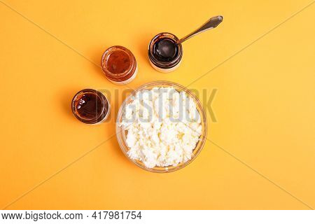 Grainy Cottage Cheese In Bowl With Different Jams On Orange Background.