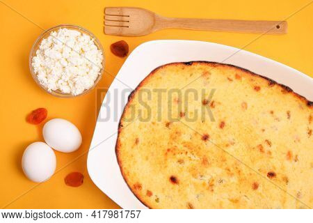 Cottage Cheese Casserole In A Baking Dish With Ingredients On An Orange Background.