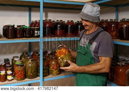 Man Satisfied With The Result Of His Work. He Watches The Shelves With Marinated Veggies In Glass Ja