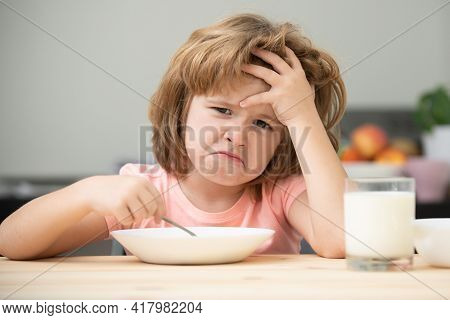 Unfocused Little Boy Having Soup For Lunch. Unhappy Caucasian Child Sit At Table At Home Kitchen Hav