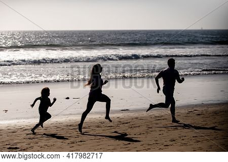 Fitness Family Running On A Sandy Beach. Sporty Family Father, Mother And Baby Son Running Together.