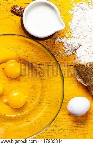 Ingredients For Making The Dough. Milk, Chicken Eggs And Flour On A Yellow Table. The Process Of Pre
