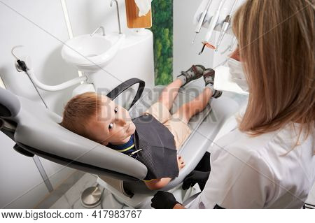 Boy Sitting In Dental Chair And Looking At Camera. Woman Dentist In Medical Mask Looking At Cute Chi