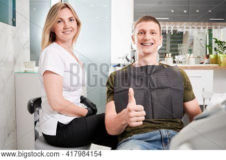 Young Man With Dental Braces On His Teeth Visiting Dentist Office. Happy Man Wearing Black Bib, Sitt