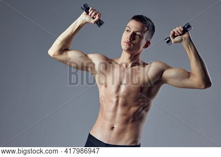 Athletic Muscular Man With Muscular Body Dumbbells In The Hands Of Biceps Workout