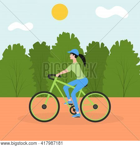 Young Sports Girl Rides A Bicycle In The City Park. The Concept Of Outdoor Activities In The City. C