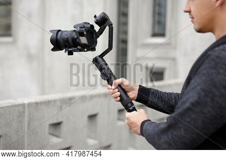 Filmmaking, Hobby And Creativity Concept - Close Up Of Professional Male Videographer Shooting Video