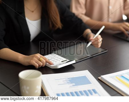 Businesswoman Hand Working With Calculator And Digital Tablet On Meeting Table
