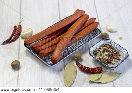 Appetizing Smoked Sausages On A Plate With Blue Pattern With Hot Peppers On A Light Grey Wooden Back