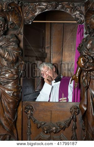 Priest sitting in 17th century confession booth listening to the repentant