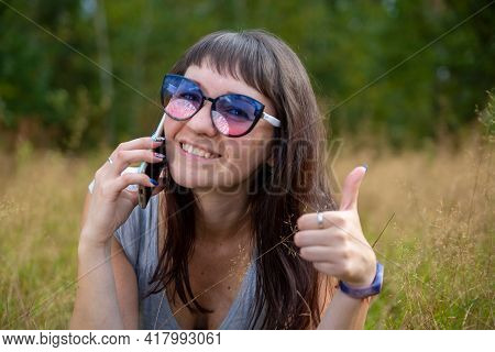 Beautiful Young Woman With Glasses Talking On The Phone And Smiling. Young Adult Girl Showing Thumb