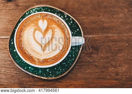 High Angle View Of A Cup Of Hot Latte Coffee On The Wooden Table. A Latte Is A Coffee Drink Made Wit
