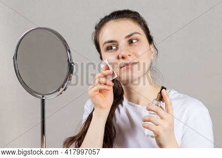 A 25-year-old Woman Holds A Face And Neck Tonic And A Cotton Pad. Anti-wrinkle Skin Care, Vitamins A