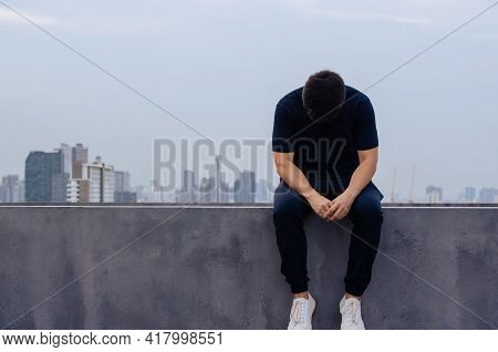 Asian Miserable Depressed Man Sit Alone With City Background. Depression And Mental Health Concept.