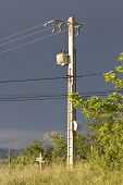 high voltage overhead power cables against stormy sky poster