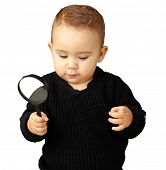 Baby Boy holding a magnifying glass against a white background poster