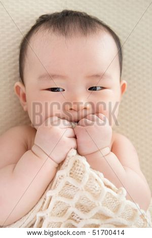 Adorable six months old teething Asian baby girl lying on bed biting blanket.