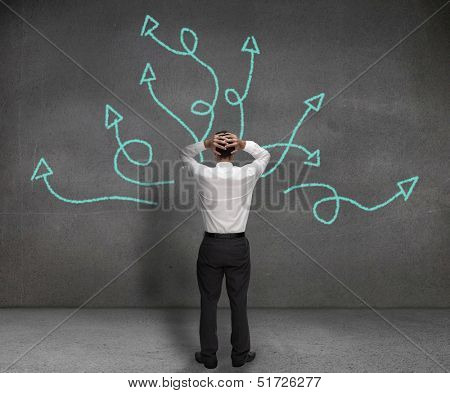 Stressed businessman looking at arrows drawn on a wall poster