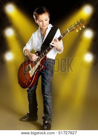 A young white boy playing on the electric guitar on the stage with bright yellow projector behind him poster