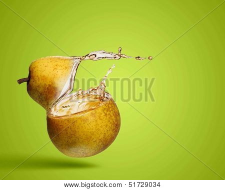 Image of juicy pear in splashes against color background