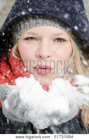 Young Blond Woman Blows In A Handful Of Snow