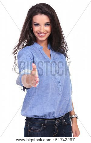 young casual woman offering a handshake while smiling for the camera. on white background