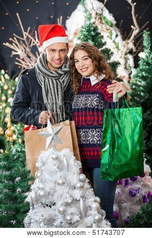 Portrait of happy young couple with shopping bags standing at Christmas store