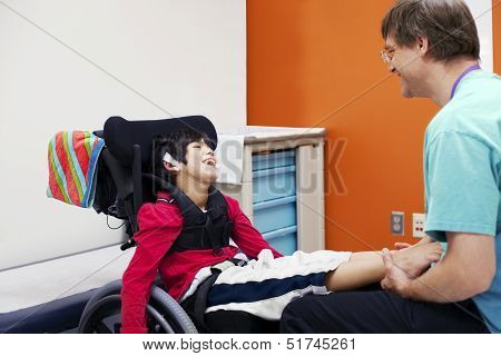 Disabled Boy In Wheelchair With His Doctor