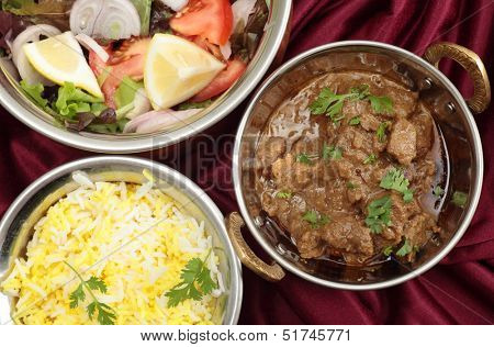 Indian copper dishes with homemade beef rogan josh, white and yellow rice and a salad, seen from above