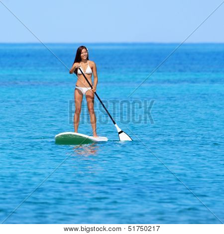 Paddleboarding beach woman on stand up paddleboard surfboard surfing in ocean sea on Big Island, Hawaii. Beautiful young multiracial Asian Caucasian woman in bikini doing water sports on vacation.