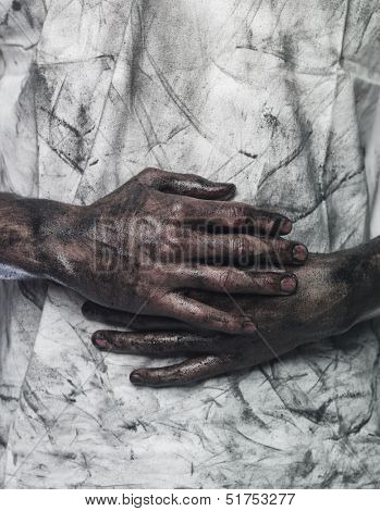 Very dirty hands in front of a dirty shirt