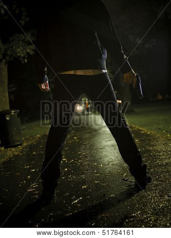 Man treating two women with a gun at night