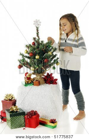 A barefoot kindergartner decorating her own tiny Christmas tree.  On a white background.