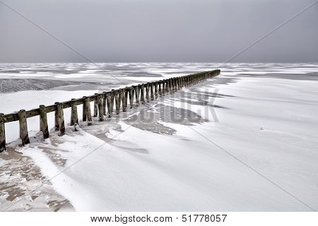 Old Wooden Breakwater On Frozen Ijsselmeer