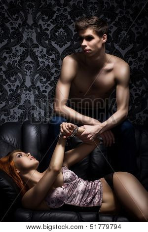 Young couple in bdsm action on the leather sofa poster