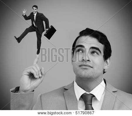 Thoughtful businessman showing shrunk colleague with his briefcase dancing on his finger