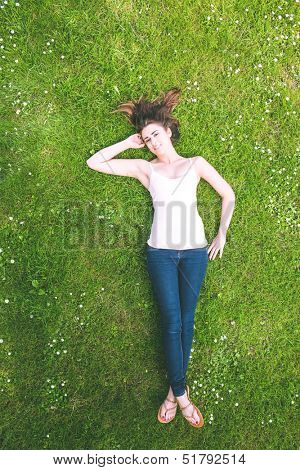 Cute brunette woman lying on a lawn smiling at the camera