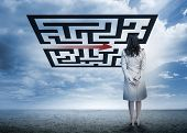 Businesswoman standing looking at arrow through qr code in cloudy desert setting poster